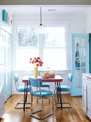 A 1950s-era laminate table and vinyl chairs set this cottage kitchen's vivid color scheme, which includes white, turquoise, and red. The overall look is one of fun and whimsy.