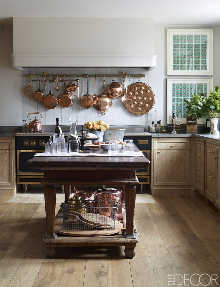 Copper pots from Eve Stone Antiques hang above a Diva de Provence range in the kitchen; the circa-1700 table is Swedish, the Portuguese limestone countertops are by Solar Antique Tiles, the custom cabinetry is limed oak, and the antique wood floor is from Baba.   - ELLEDecor.com