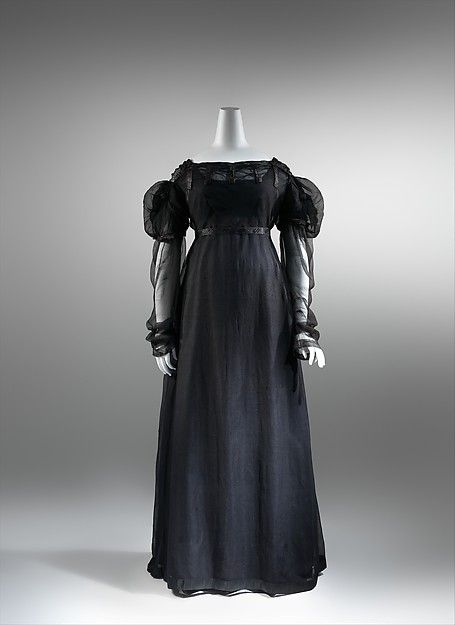 Dress 1820 Mourning - This mourning dress incorporates the puffed sleeves and ornate hem details that defined 1820s fashions. Standards for family mourning were modeled after court conventions. Upon a royal death in England, orders were issued detailing the duration of each phase of mourning and appropriate materials. Silk satins, taffetas, and velvet, considered too glossy and sumptuous for the first stage, were permitted later.