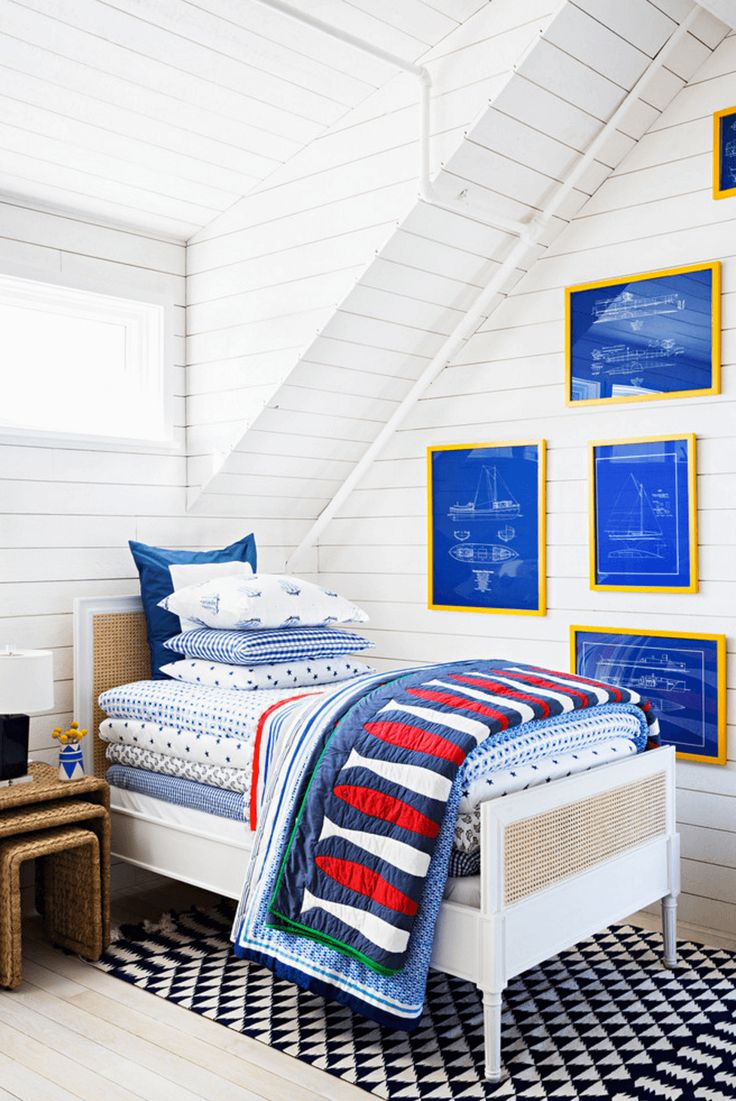 This bed is literally stacked, and we love it. Nautical goes whimsical while a pile of patterns on a bright white canvas. The blueprints in their yellow frames complement the space perfectly