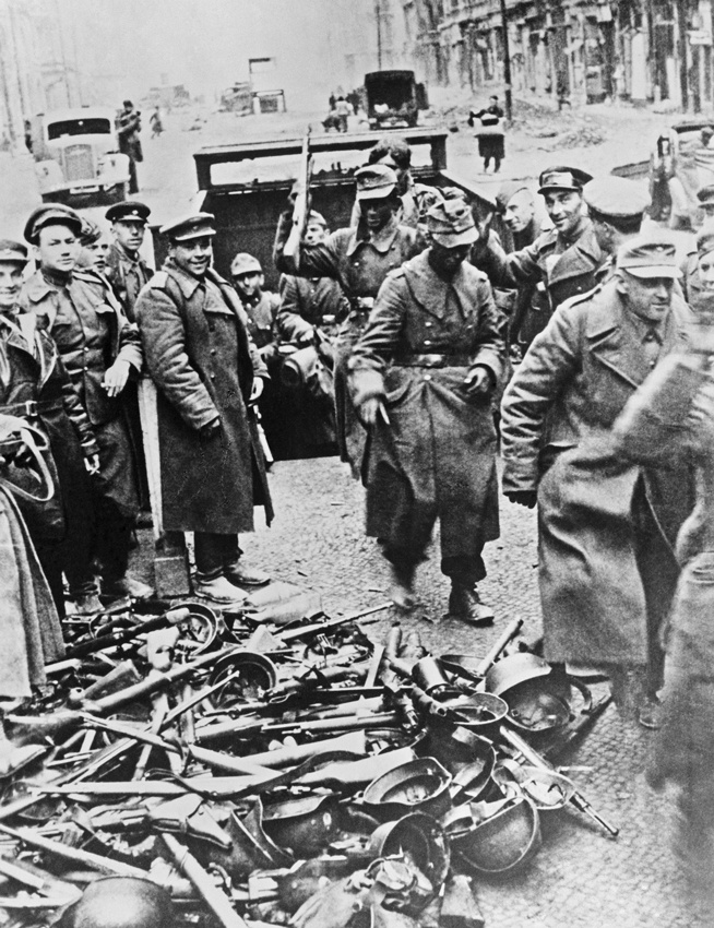 Berlin Capitulation, May 1945: The last remnants of Berlin's defenders emerge from a basement to surrender their weapons to Soviet troops smiling for the camera.