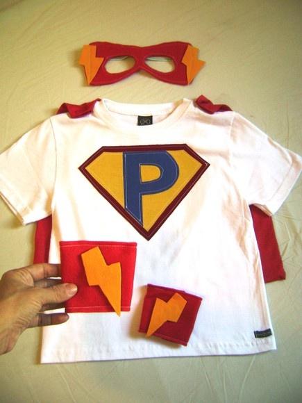 Camiseta em malha com aplique de emblema com a inicial da criança.  Capa nas costas em malha removível , presa com velcro.  Máscara e braceletes em feltro.  Pode ser feita em outro tamanho, cor ou emblema R$59,00