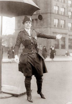 This picture was taken in 1918, and shows a police woman. The woman appears to be directing traffic, but she does have a gun in a holster on her belt. I am wondering if this had been a traditional job for a woman or if perhaps World War I created a shortage of men, and led to women taking on new roles