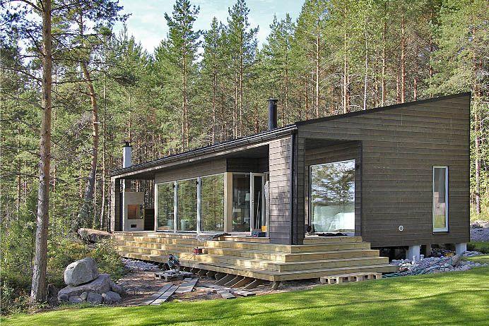 Vähäeleisen tyylikäs moderni puuhuvila ja saunarakennus katselevat kaunista järvimaisemaa.
