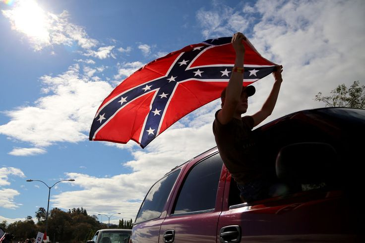 Chance White waves a Confederate battle flag at Roseburg Regional Airport. More than 200 gun-rights activists protested President Barack Obama's visit.