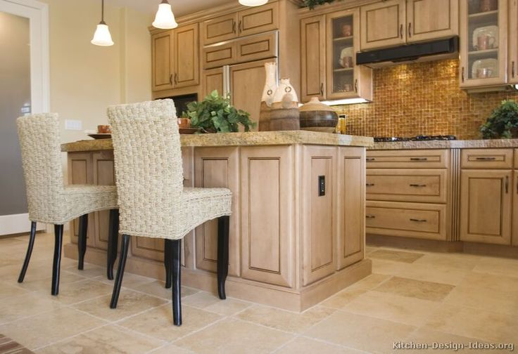 A traditional kitchen featuring whitewashed maple wood cabinets, an island with fabric stools, and a mosaic tile backsplash