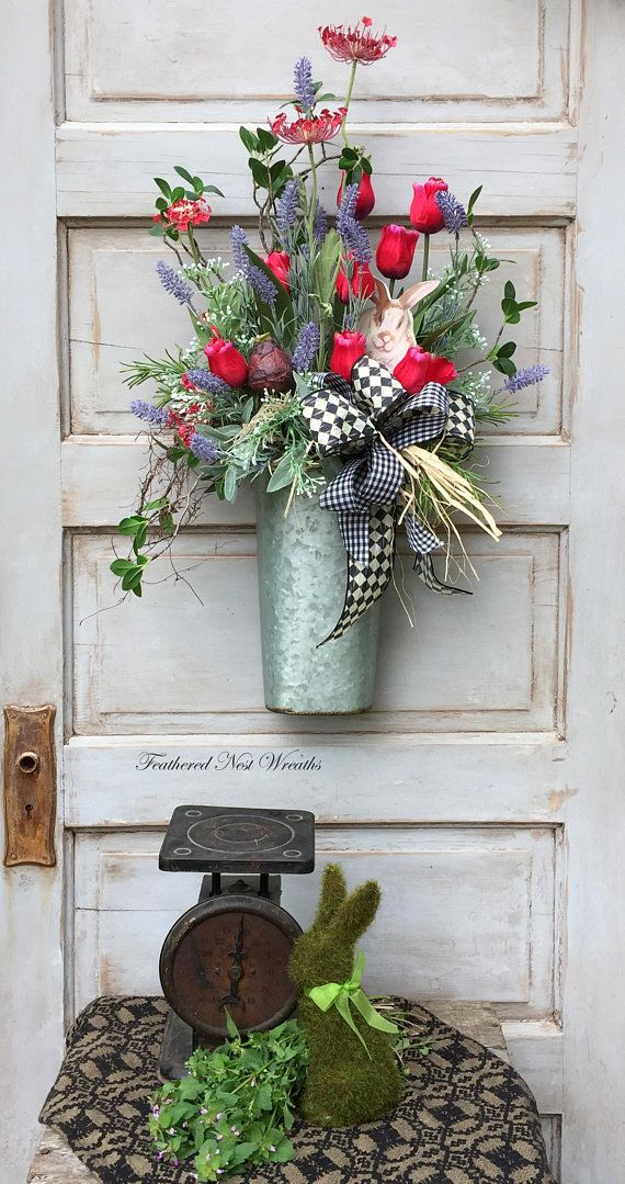 This Spring Door Basket is made in a Galvanized Container. I have Filled it with Red Tulips, Red Spider Lilies, Myrtle Branches, Lavender, Rosemary, Small White Spring Flowers, a Faux Tulip Bulb and Greenery. I added a little Bunny MDF Figure in the Arrangement, this can be