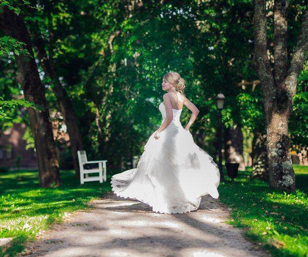 Невеста в подвенечном платье кружится на тропинке в парке