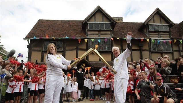 Torchbearer Peter Wyatt passes the Olympic Flame to Torchbearer Camilla Hadland outside Shakespeare's Birthplace in Stratford-Upon-Avon during Day 44 of the London 2012 Olympic Torch Relay.