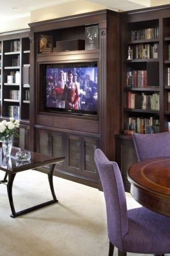 """An attractive large dark wood fluted formal """"built-in"""" makes space for a large TV and books with nice glass doors below for other things."""