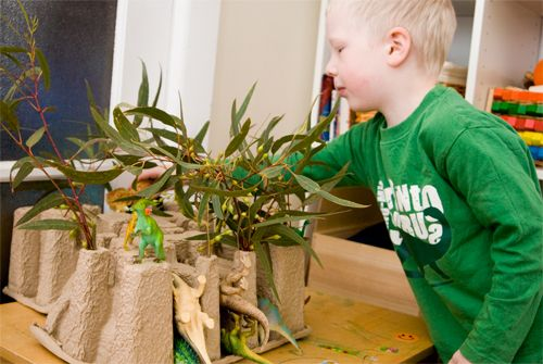 dinosaur play - great use of packaging to make mountains and background