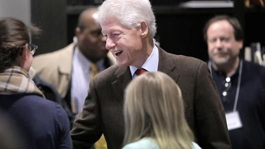 President Bill Clinton greets people inside the Newton Free Library, a polling place, in Newton, Mass., during Massachusetts primary voting on March 1, 2016.