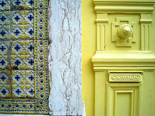 Yellow,white and blue azulejos and a yellow door in Lisbon, Potugal √