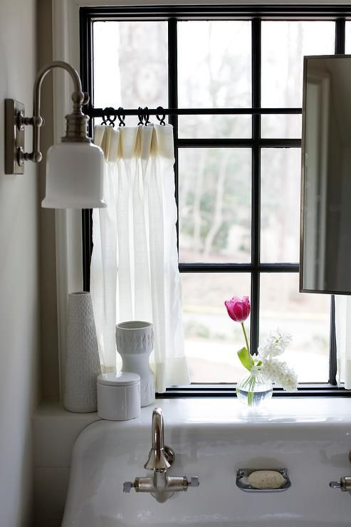 Gorgeous cottage bathroom features a trough sink fitted with two vintage satin nickel faucets tucked under a window placed in front of windows dressed in white cafe curtains.