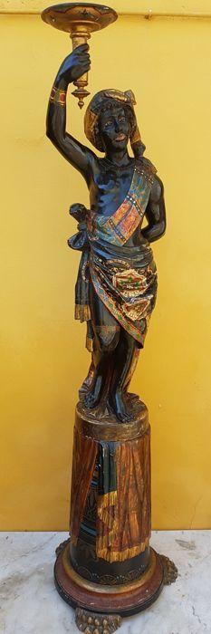 Fijn gesneden houten beeldje van een Moor, afkomstig uit Venetië, ca. 1870-1880, in hout, gelakt, polychroom en verguld, fijn beschilderd met florale motieven. Een museum-item in een goede staat van bewaring, gesneden, ebonized en geschilderd, gemodelleerd naar een Negroide figuur met borstelige krullend haar, op een voorgevormde basis liggend op drie lion's voeten. Zoals aangetoond in de foto's, is het beeld verdeeld in twee delen, met een totale hoogte van 180 cm en een basis 50 cm....