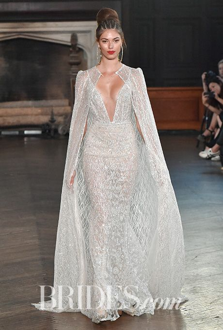 Brides.com: . Style 17-130, fully embellished lace on netting dress, plunging neckline, strap sleeves, open back and an optional matching embellished cape by Berta