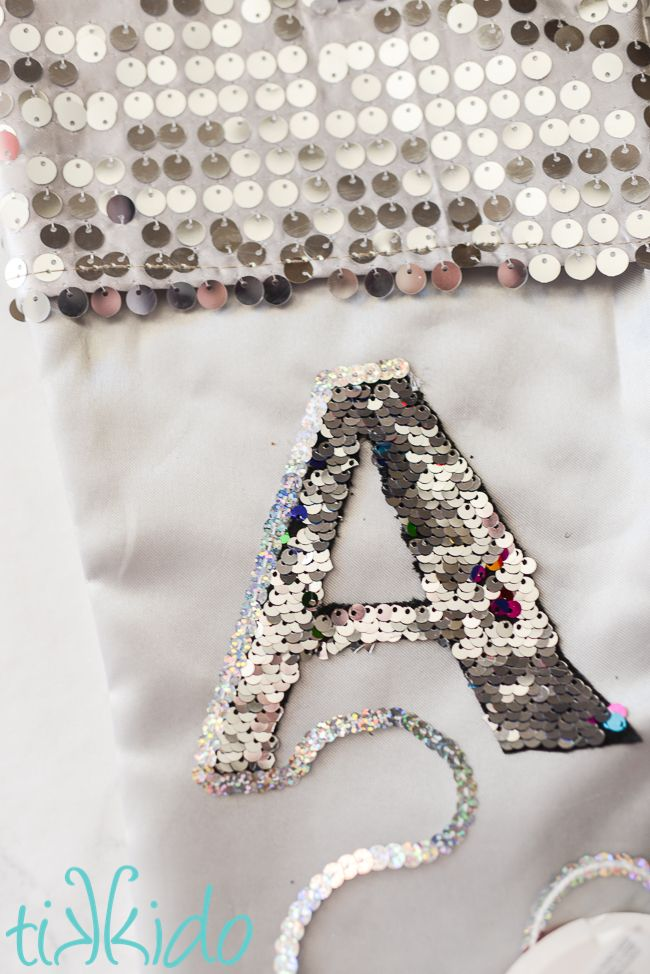 7174eea0a3a Mermaid sequin fabric monogram on a silver stocking being outlined by  silver sequin cord.
