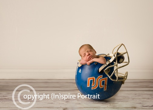 Newborn in his daddys college football helmet
