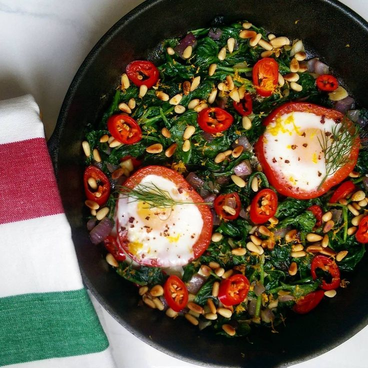 #Lunchtime. Sauteed spinach, garlic, onions and chillies, topped with toasted pine nuts and lemon zest, served alongside fried eggs in sweet pepper rings. #LodgeCastIron @zimmysnook