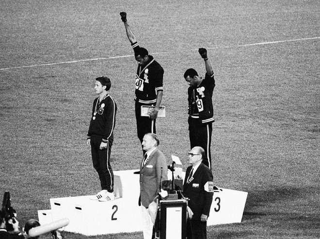 JO 1968: Les coureurs américains Tommie Smith2 et John Carlos arrivés premier et troisième du 200 mètres protestent contre la ségrégation raciale aux États-Unis en baissant la tête et en pointant, lors de l'hymne américain, leur poing ganté de noir vers le ciel, sur le podium de la remise des médailles.