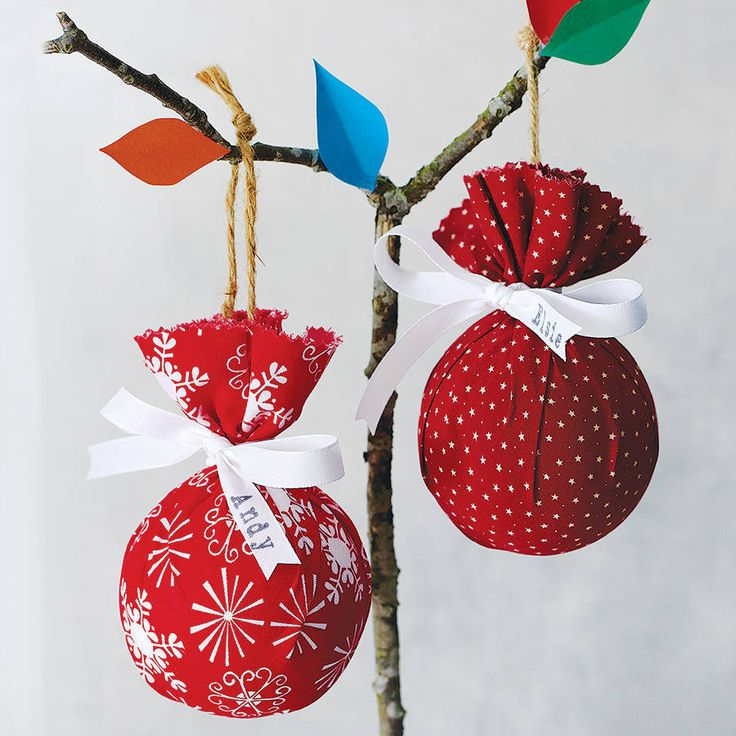 A homespun alternative to Christmas decorations creating a pleated, gathered effect fabric parcel bauble.Available in five fabrics - snowflake, red star, stockings, red polka dot and mini star. You can personalise your bauble with a name printed onto the white ribbon bow tied around the neck of the bauble. Simply enter your name in the space provided.The fabric baubles make a lovely personal gift, hand-printed with a name or nickname of your choice. They look lovely hung on a Christmas tree…