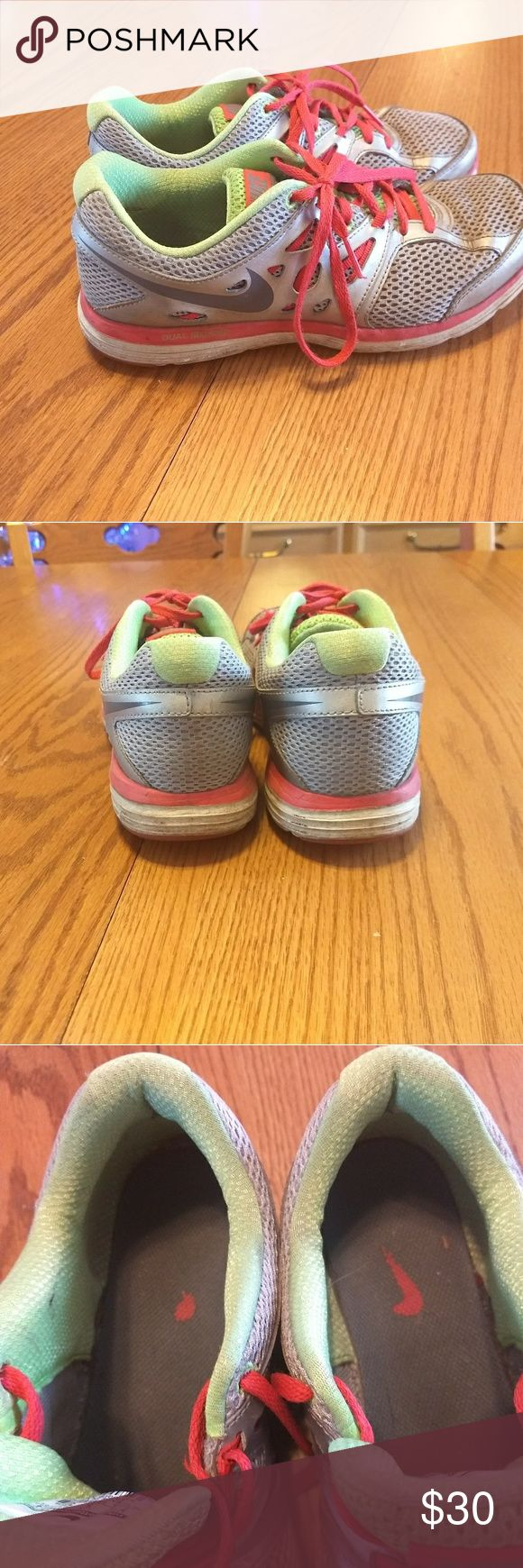 Women's Nike Dual Fusion sneakers Size 7.5 silver gray, orange and green Dual Fusion running shoes. Still loads of wearability. No rips in the toe mesh, no wear thru in the fabric of inside heels. Soles in great shape with even wear. Nike Shoes Athletic Shoes