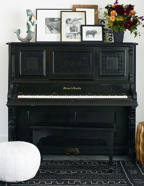 Decor - An antique piano topped with a mermaid sculpture and a collection of framed art