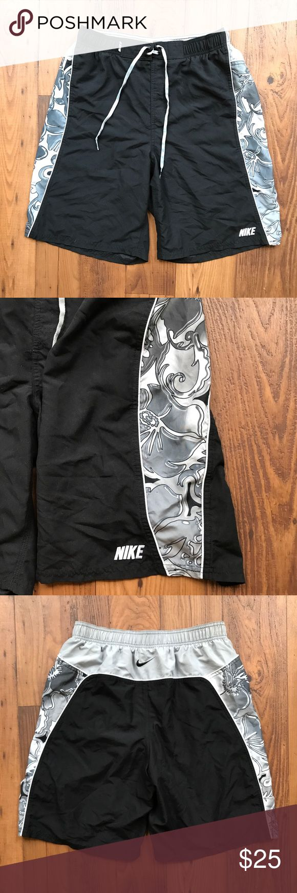"""Nike Black Swimming Trunks Hawaiian Floral Sides Men's Nike swimming trunks. They are black with gray side panels that have Hawaiian flowers. Tie around the waist. Pockets. Lined. Size medium. From top to bottom the trunks are about 20.5"""". Nike Swim Swim Trunks"""