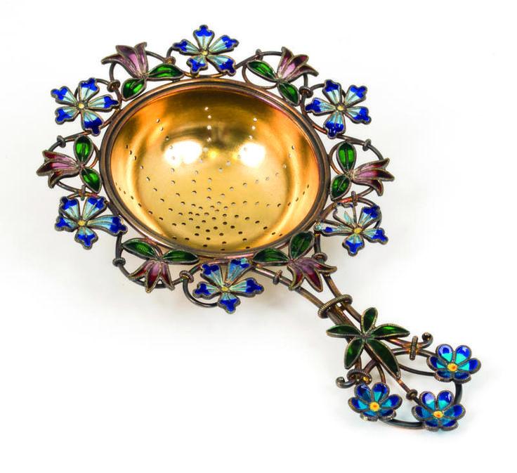 Gustav Gaudernack design for David Andersen. Tea strainer in gilt silver with flowers in plique-a-jour enamel- 1893-1895.