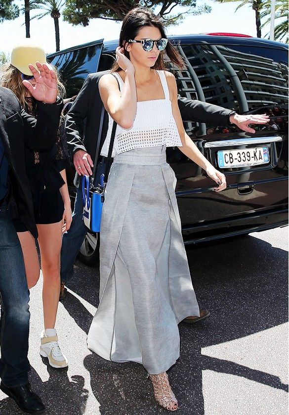 Kendall Jenner wears a cropped eyelet top, maxi skirt, strappy sandals, and mirrored sunglasses