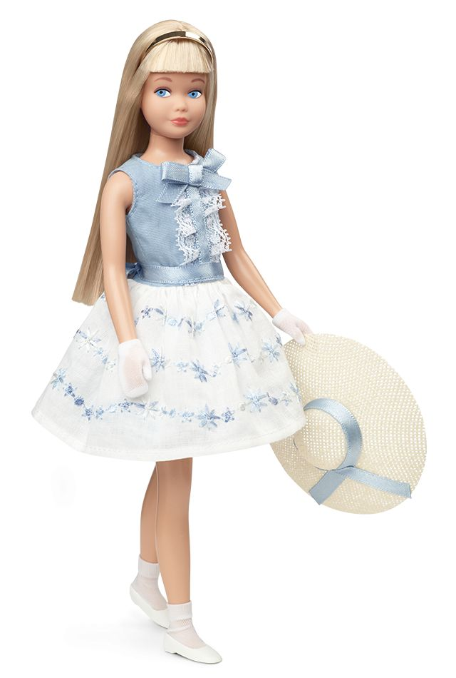 """Happy birthday! Skipper doll wears a re-creation of 1965's """"Happy Birthday"""" fashion from the 1900 Series. Her sleeveless dress features white lace embellishments and blue floral embroidery. A """"straw"""" boater hat with a blue ribbon tops off her adorable ensemble. Also included are replicas of the original accessories: a """"wrapped"""" gift, birthday """"cake"""" with """"candles"""", napkins and more!"""