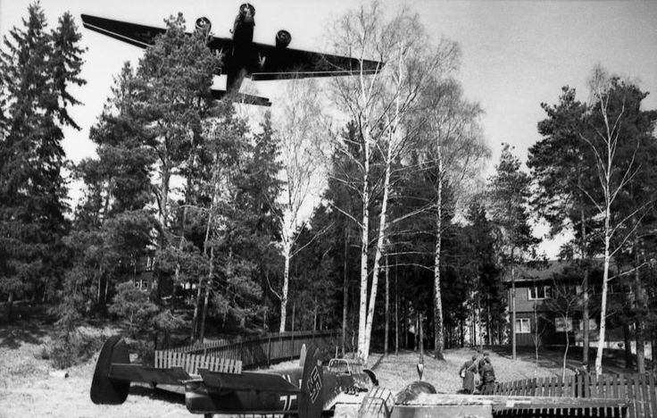 April 9. 1940. Fornebu airport, Oslo. In the foreground a Messerschmitt Bf 110  which overshot the runway and came to rest in the garden of a house. A Junkers Ju 52/3m plane flies low over the location