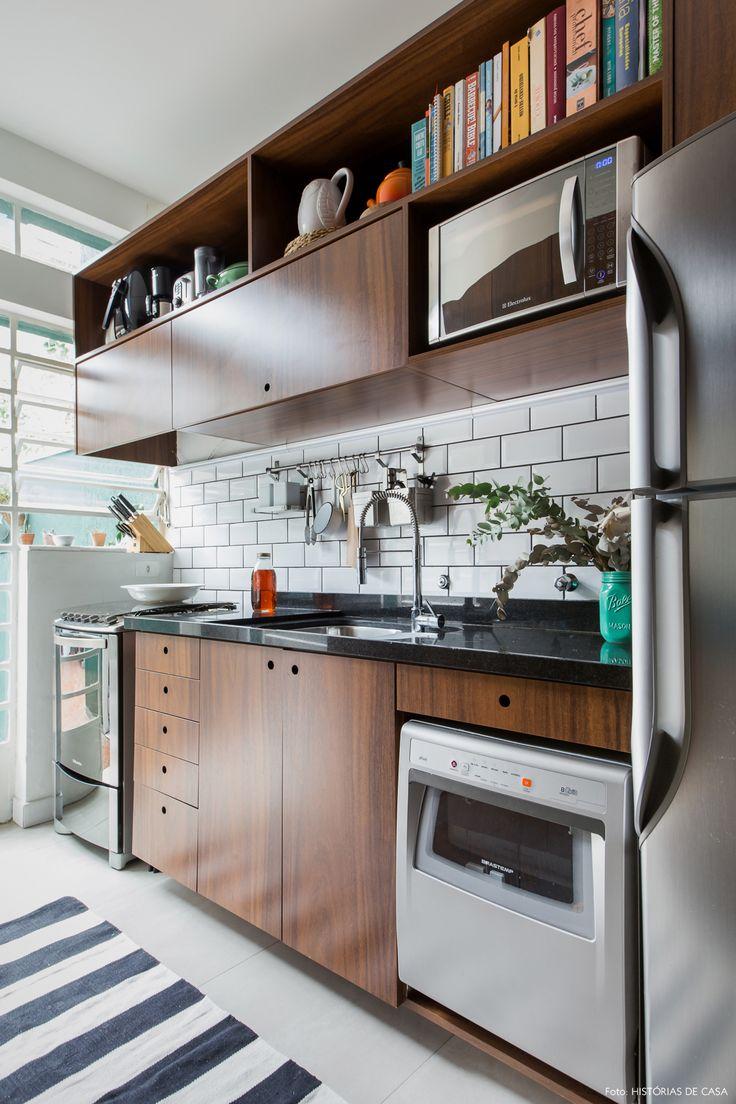 Cozinha tem armários de madeira, subway tiles com rejunte escuro e passadeira listrada.