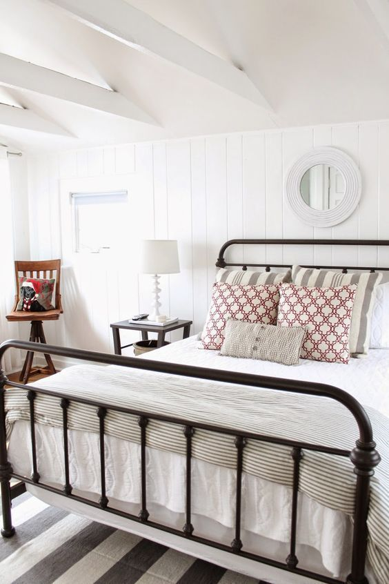 Pretty bedroom with iron bed and planked walls