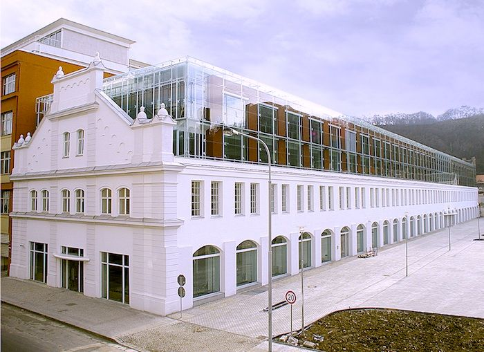 The industrial space is located in the Prague 8 municipal district of Prague. The original building has been preserved and its base renovated. The new roof is of glass, and red stucco arcades highlight the composition of the existing ground floor. The aim here is to maintain a dialogue between light and shadow, solidity and transparency; between the language of classical architecture and modern materials.