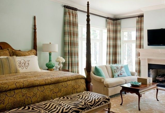 balance a room with an offset window. The drapes and furniture grouping at one end have the same visual weight as the bed.