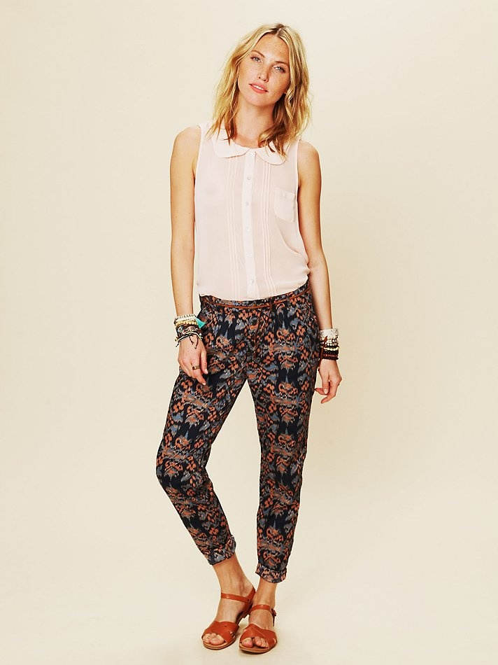 Vintage-inspired floral patterned trouser pants. High-waisted style with slit fit throughout leg. Button fly closure. Two front pockets. Pleating below the waist. One faux slit pocket in back.