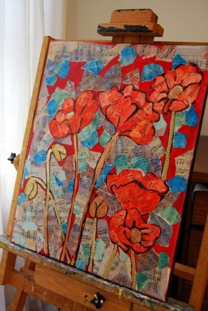 Bright and stunning flower painting depicts ember-glow coral red poppies in a garden. The background in the original painting is torn piano sheet music that has been tinted with watercolor and used as a collage element over acrylic and oil on canvas. When you get close up, you can see the music which makes this mixed media art truly a conversation piece.