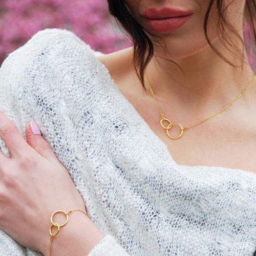 Złoty naszyjnik i bransoletka zdwoma połączonymi kółeczkami, biżuteria gwiazd, karma, obrączki / Golden necklace and bracelet with karma, jewellery, jewelry, celebrity