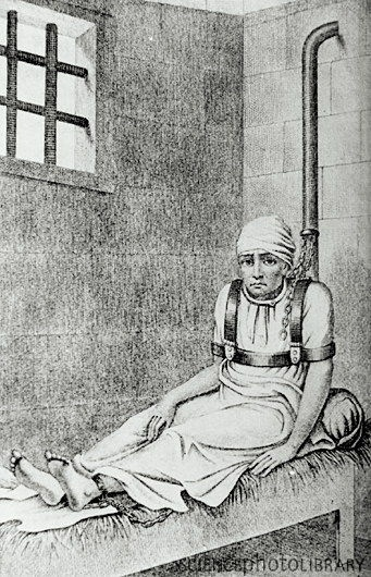 Female patient chained to a post in an 18th century mental asylum. Methods of constraint such as this were often used because patients were seen as being dangerous. It also made the job easier for the few warders assigned to look after the patients. In 1792, the French physician Philippe Pinel was the first to realize that such deprivation of movement & light actually worsened patients' mental conditions.