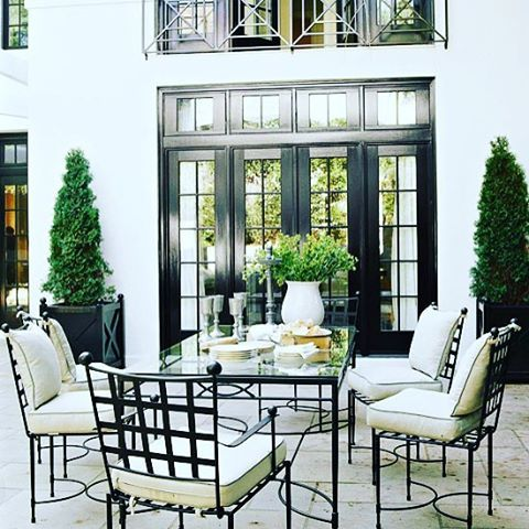 { S O P H I S T I C A T I O N } The monochromatic scheme of this alfresco patio screams sophisticated elegance.  We love the Hamptons Planters featuring topiary buxus framing the cross french doors and the use of lattice chairs which work back beautifully with the entryway.  A gorgeous feature yet again from @traditionalhome #sophisticatedstyle #monochromatic #blackandwhite #outdoorliving #patio #patiofurniture #outdoordecor #planter #buxus #lattice #blackdoor #classicstyle #frenchcountry…