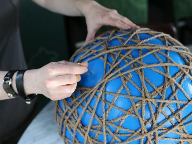 Feel the rope to ensure the glue has hardened. Next, use 2â picture nail to pop the rubber ball.