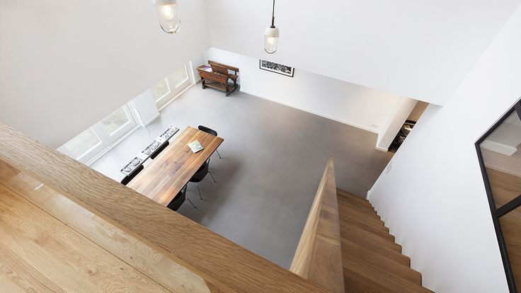 Industrial dining area with grey cast floor and wooden staircase, deisgn by BNLA architects