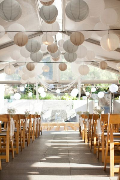 Mix white, dove grey and latte hanging lanterns for this subtle and elegant feature to detract away from the marquee poles.
