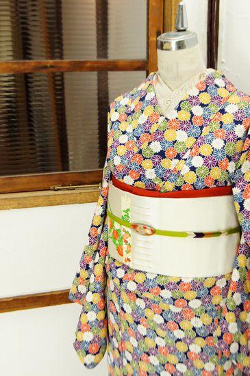 芥子色や朱色、藍や若草色、紫、白の色どり豊かな菊花が水玉のように染め出された正絹縮緬の袷着物です。