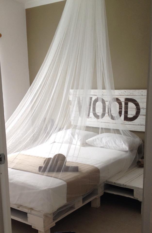 una cama hechas enteramente de tarimas con su cabecera tambien de tarimas recicladas