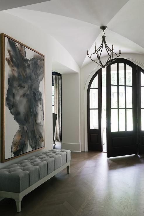 A black arched front door complemented with arched sidelights provides a bit of drama to a chic foyer lit by a quatrefoil light pendant and boasting a large gold and gray abstract art piece hung over a gray linen tufted bench placed on a wood herringbone floor.
