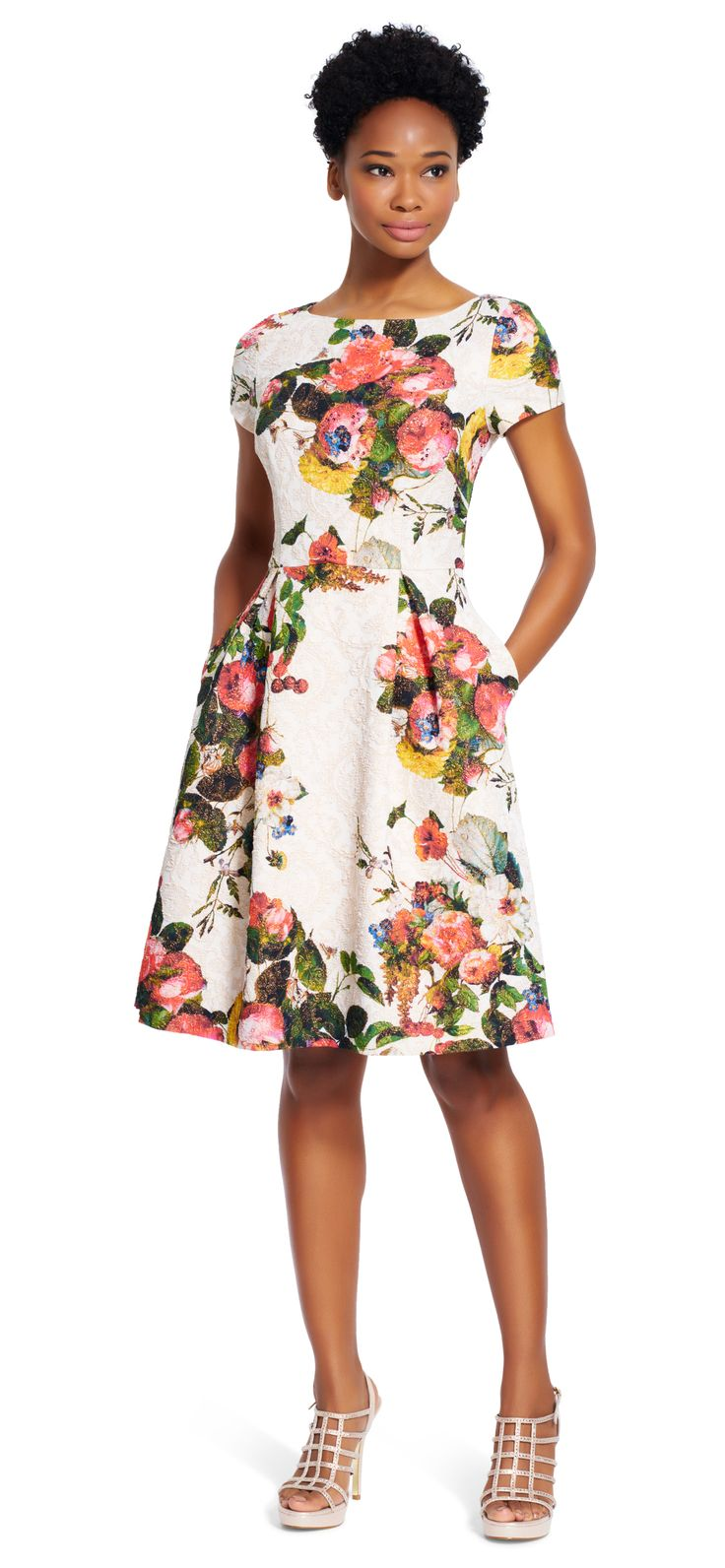 A vibrant floral print adorns a sweet fit and flare silhouette, sparkling with metallic threads throughout. Pockets at either side.
