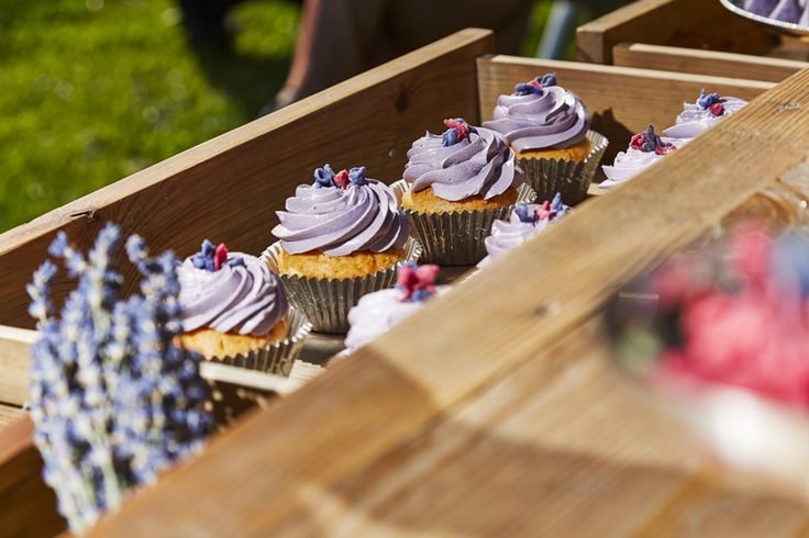 Purple frosting cupcakes picking through a drawer of our dessert table, an antique console