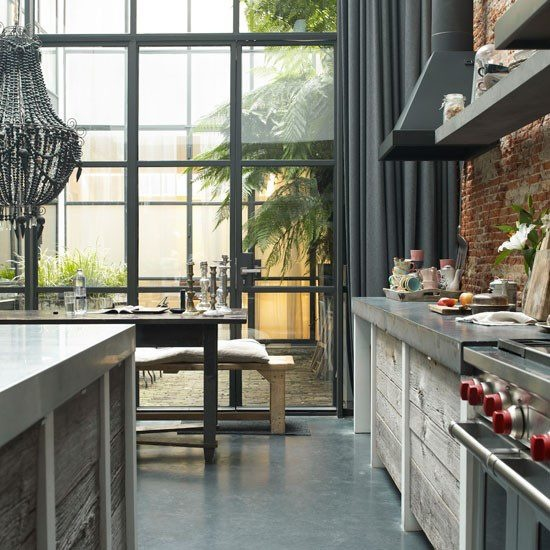 Grey and Brick, this kitchen is quite unique. Thick curtains that hang towards the floor. A mix of interior styles.